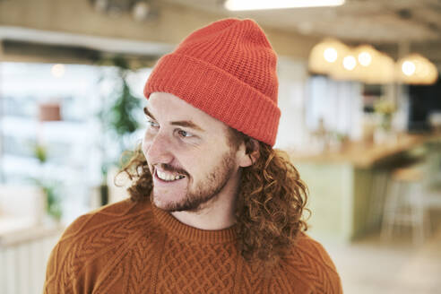 Smiling hipster man wearing red knit hat at home - FMKF06715