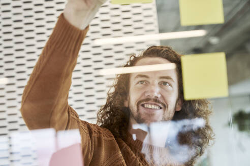 Smiling man sticking adhesive notes on glass material at home - FMKF06739