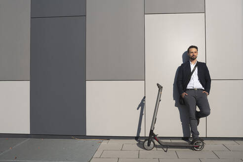 Confident entrepreneur looking away while standing by electric push scooter against wall - HMEF01168