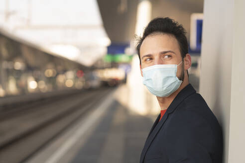 Male entrepreneur looking away while wearing protective mask on railroad platform - HMEF01180