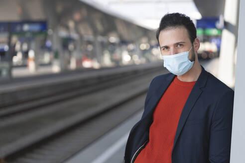 Male entrepreneur wearing protective mask on railroad station platform - HMEF01183