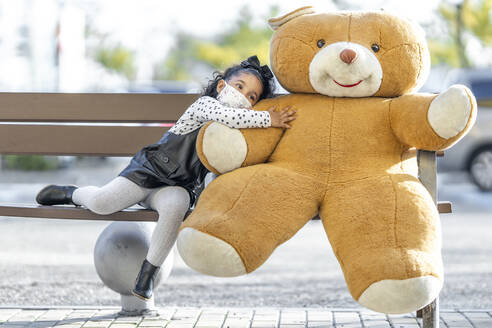Girl wearing face mask embracing teddy bear while sitting on bench - GGGF00183