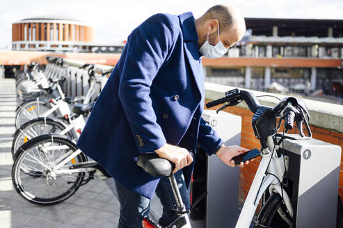 Man wearing protective face mask unlocking bicycle through smart phone on sunny day - PGF00199