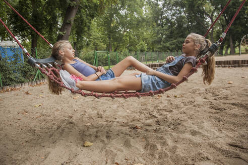 Girls relaxing on rope swing at playground - AJOF00576