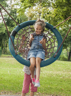 Boy pushing cheerful girl sitting on rope swing in park - AJOF00585