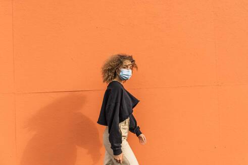 Woman wearing face mask walking against orange wall - MEF00003