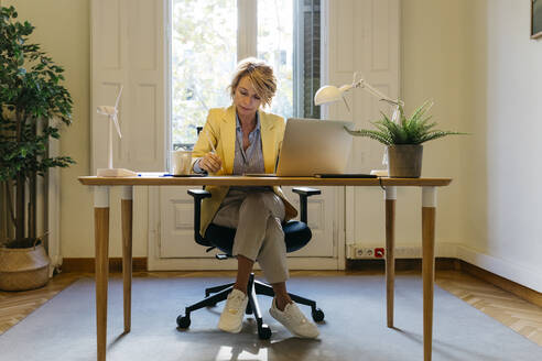 Female architect sitting with laptop while working at office - JRFF04931