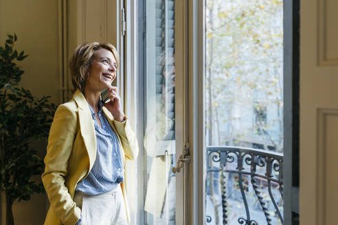 Smiling businesswoman talking on smart phone while looking through window standing in office - JRFF04940