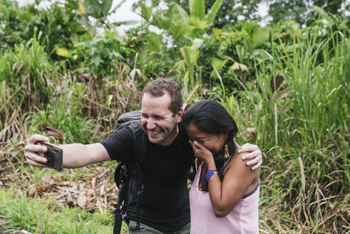 Smiling male tourist taking selfie with shy woman at Misahualli, Ecuador - DSIF00199
