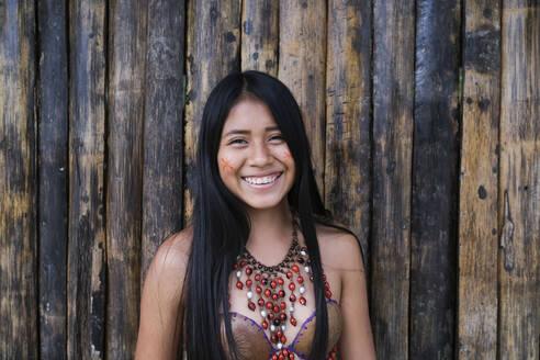 Happy young Guarani woman against bamboo wall, Misahualli,  Ecuador - DSIF00205