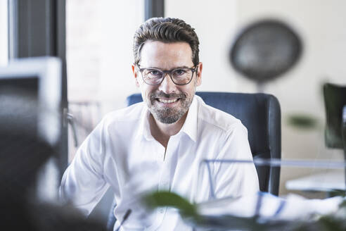 Smiling businessman sitting at office - UUF22089