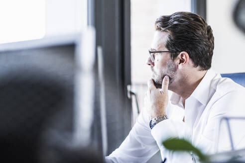 Thoughtful businessman with hand on chin looking away while sitting at office - UUF22092