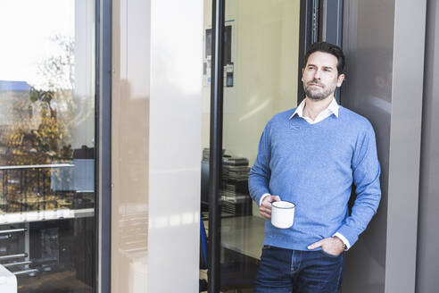 Businessman holding coffee cup while leaning on wall with hand in pocket at office entrance - UUF22116