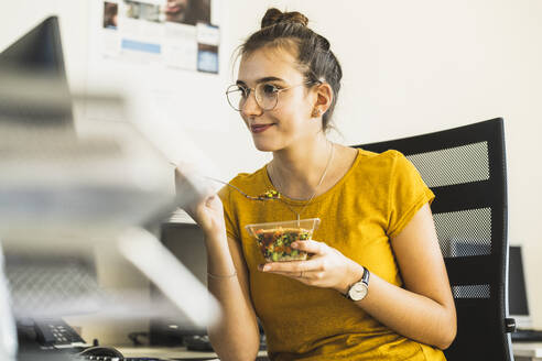 Smiling businesswoman eating food while looking at computer sitting at office - UUF22134