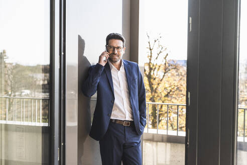 Businessman talking on mobile phone while standing by balcony at office - UUF22143