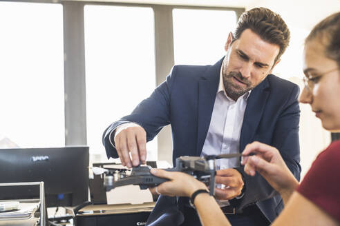 Businessman examining quadcopter with colleague at office - UUF22149