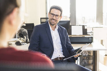 Businessman having discussion with colleague while sitting at office - UUF22155