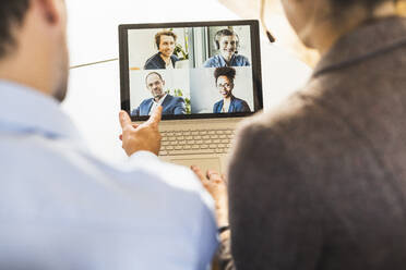 Business people attending meeting through video conference on laptop at office - UUF22161