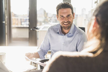 Smiling businessman working with colleague while sitting at office - UUF22167