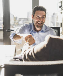 Happy businessman giving fist bump to colleague while sitting at office - UUF22170