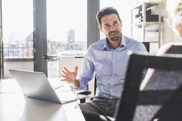 Businessman using laptop while discussing with colleague at office - UUF22173