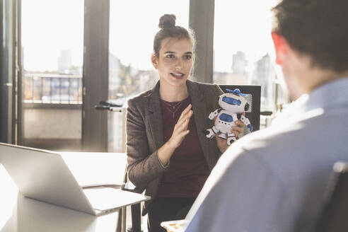 Businesswoman holding robot toy while having discussion with colleague at office - UUF22176