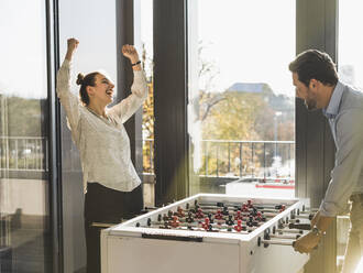 Happy businesswoman showing winning gesture while playing Foosball with businessman at office - UUF22185