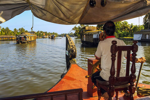 Captain on phone and steering houseboat through the backwaters on a popular backwater cruise, Alappuzha (Alleppey), Kerala, India, Asia - RHPLF17994