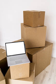 Laptop on cardboard box in new house - GIOF09686