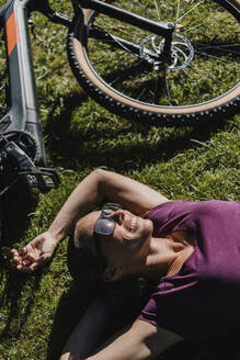 Smiling woman resting while lying on grass by mountain bike at park - DMGF00301