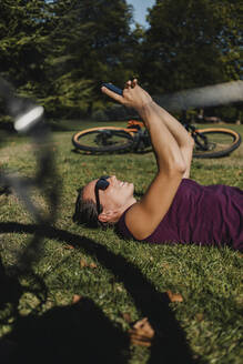 Sportswoman using mobile phone while resting on grass by electric mountain bike at park - DMGF00307