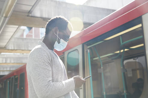 Businessman wearing protective face mask while using mobile phone at railroad station - PMF01560