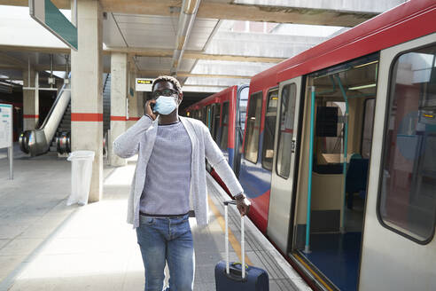 Mature businessman wearing protective face mask talking on phone at railroad station platform - PMF01563