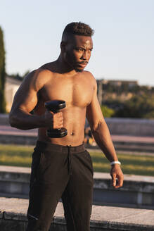 Shirtless man exercising with dumbbell while standing at park - PNAF00216