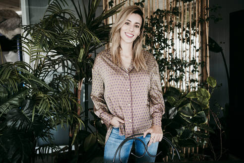 Smiling businesswoman standing against plants at creative office - EBBF01572