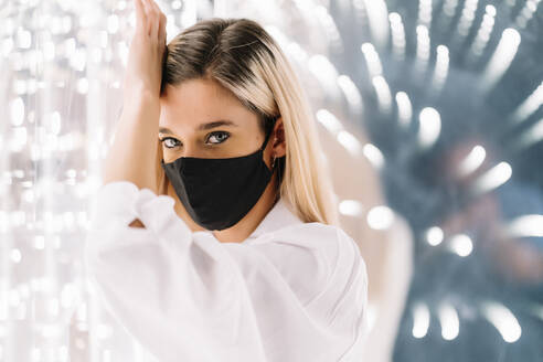 Young woman in protective face mask leaning on light wall - DAMF00623