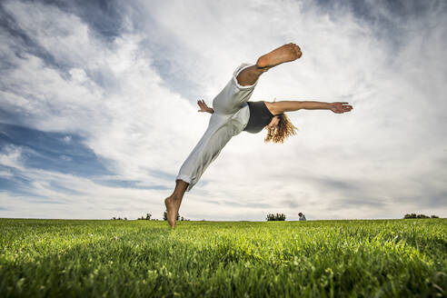 Female acrobat doing movement in park against cloudy sky - ABAYF00027