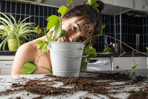 Woman leaning on flower pot at home - GGGF00217