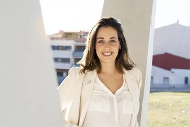 Smiling female entrepreneur in city on sunny day - AFVF07655