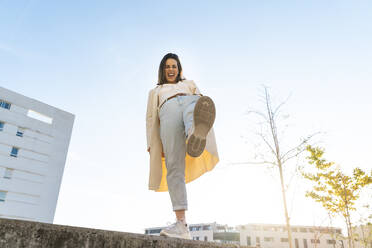 Cheerful businesswoman with leg-up standing on retaining wall in city against sky - AFVF07691