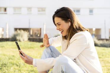 Happy female entrepreneur doing video call through smart phone while sitting on grass in garden - AFVF07694