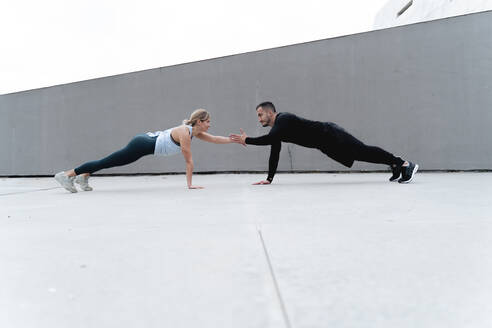 Young couple giving high-five while doing plank against wall - FMOF01264