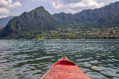 Kayak boat floating on Lake Idro in front of mountains - MAMF01424