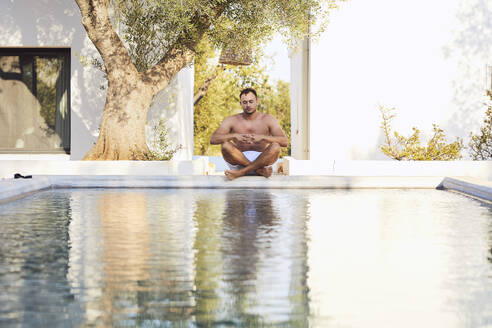 Shirtless young man meditating at poolside in backyard - UKOF00072