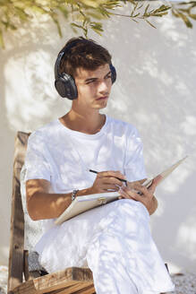 Thoughtful young man with book and pen listening music through headphones against white wall - UKOF00093