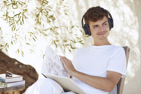 Smiling young man with book looking away while listening music through headphones in backyard - UKOF00096