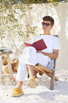 Young man relaxing on chair while holding book against wall - UKOF00102