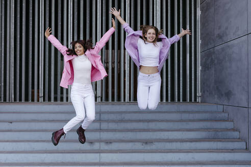 Cheerful sisters jumping on steps against wall - TCEF01319