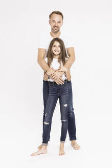 Smiling mature man with daughter standing against white background - SDAHF00998