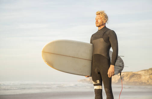 Blond man wearing wetsuit carrying surfboard while looking away at beach against sky - KBF00637